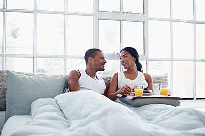 Buy stock photo Shot of a smiling young couple enjoying breakfast in bed together