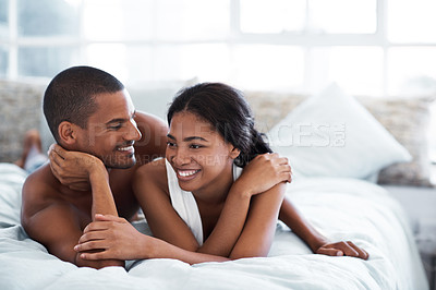 Buy stock photo Shot of a young couple laughing together while lying in bed