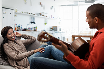 Buy stock photo Shot of a young man serenading his wife with a guitar