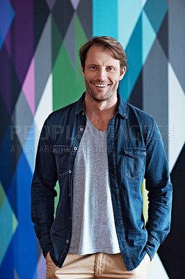 Buy stock photo Portrait of a smiling mature man standing in front of a colorful wall