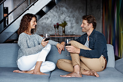 Buy stock photo Shot of an affectionate mature couple drinking wine while sitting on a sofa in their living room
