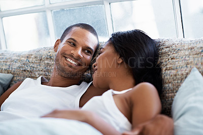 Buy stock photo Shot of a happy young couple talking together while lying in bed