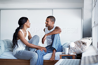 Buy stock photo Shot of a happy young couple talking together while sitting on their bed
