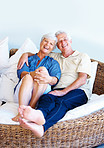 Senior couple sitting on a sofa and smiling