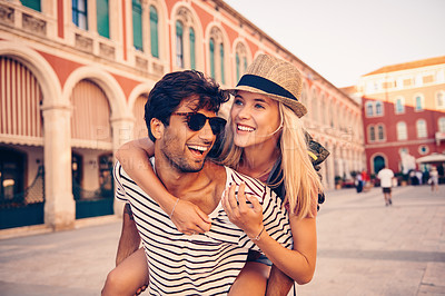 Buy stock photo Shot of a young man piggybacking his girlfriend through a foreign city