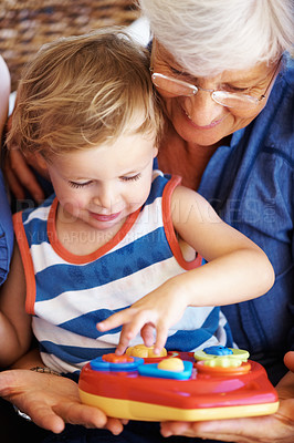 Buy stock photo Little kid and grandmother playing with a toy