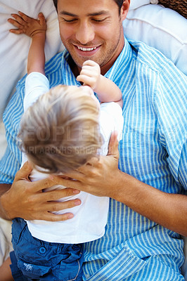 Buy stock photo Father relaxing on a sofa and holding his son