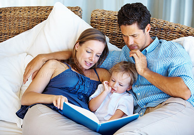 Buy stock photo Family of three relaxing on a sofa with mother reading a story to her son