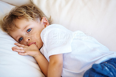 Buy stock photo Cute little kid lying on a sofa with thumb in mouth and looking away - copyspace