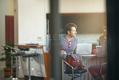 Buy stock photo Shot of colleagues working together on a laptop in a modern office