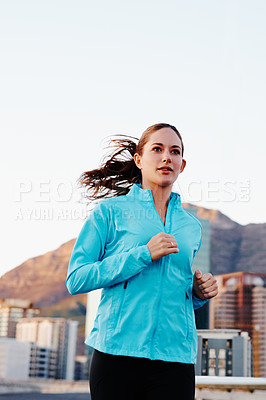 Buy stock photo Shot of a young woman out for a run in the city