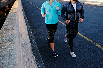 Buy stock photo Cropped shot of a young couple out for a run in the city