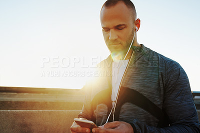 Buy stock photo Shot of a young man listening to music while out running