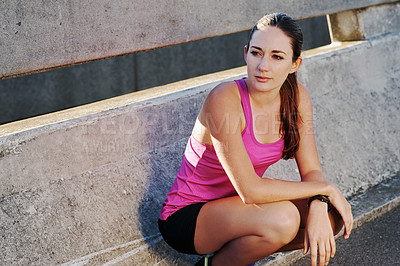 Buy stock photo Shot of an athletic young woman taking a break from her run in the city