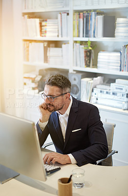 Buy stock photo Shot of a businessman working at his computer in an office