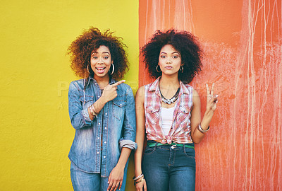 Buy stock photo Portrait of two young friends posing against a colorful background