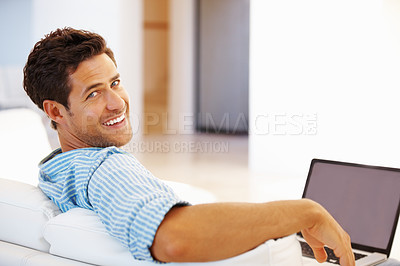 Buy stock photo Portrait of man sitting on a sofa at home using laptop and smiling