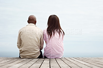 Buy stock photo Rearview shot of a young couple sitting side by side on a boardwalk looking at the ocean