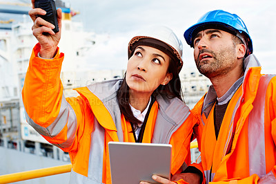 Buy stock photo Shot of two people talking over a digital tablet while standing on a large commercial dock