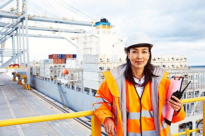 Buy stock photo Portrait of a woman in workwear holding a walkie talkie while standing on a large commercial dock