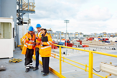 Buy stock photo Shot of workers talking over a digital tablet while standing on a large commercial dock
