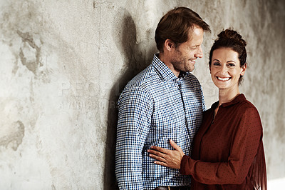 Buy stock photo Portrait of an affectionate couple leaning against a wall