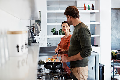 Buy stock photo Shot of a mature couple cooking together in their kitchen