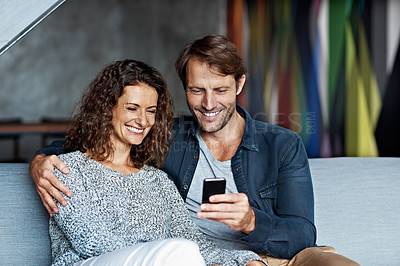 Buy stock photo Shot of a mature couple using a cellphone while sitting on their living room sofa