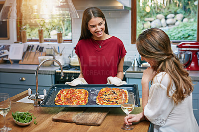 Buy stock photo Shot of two friends eating pizza and drinking wine in the kitchen