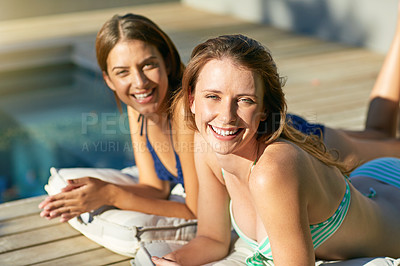 Buy stock photo Portrait of two young women in bikinis sunbathing by a swimming pool