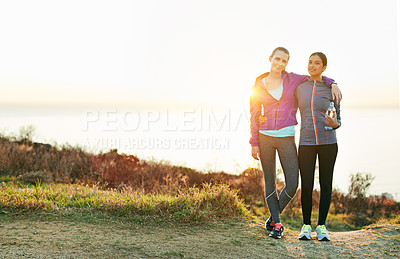 Buy stock photo Portrait of two young friends standing arm in arm after a run