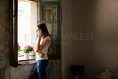 Buy stock photo Shot of a young woman talking on her cellphone while looking out of a window