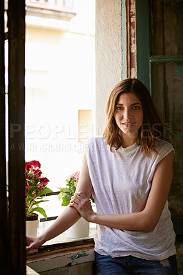 Buy stock photo Portrait of an attractive young woman standing by a window in her home