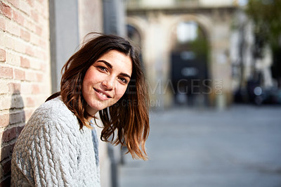Buy stock photo Portrait of a smiling young woman leaning against a brick wall outside