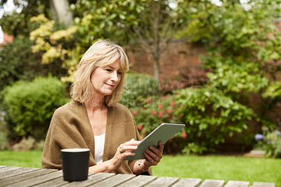 Buy stock photo Shot of a mature woman sitting at a table in her yard using a digital tablet