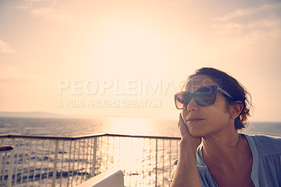 Buy stock photo Shot of a young female tourist catching the sunset on a balcony overlooking the beach