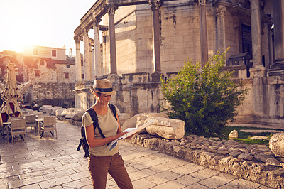 Buy stock photo Shot of a woman looking at a map while out sightseeing in a foreign city