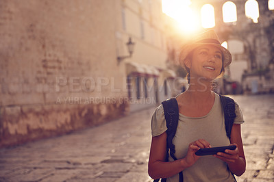Buy stock photo Shot of a young woman using her tablet while out exploring a foreign city