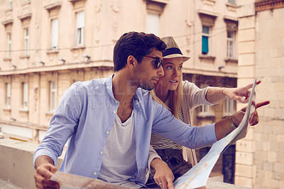Buy stock photo Shot of a young couple with a map out sightseeing in a foreign city