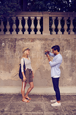 Buy stock photo Shot of a young man taking a photo of his girlfriend while they're exploring a foreign city