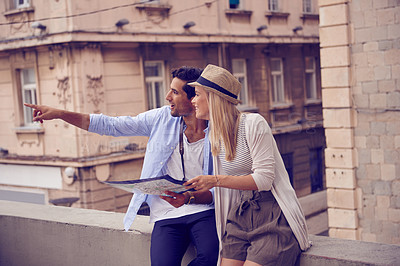 Buy stock photo Shot of a young couple with a map exploring a foreign city