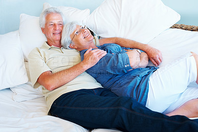 Buy stock photo Happy senior couple relaxing together on a sofa and smiling