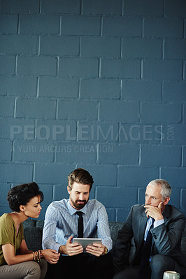 Buy stock photo Shot of a group of coworkers working together with a digital tablet