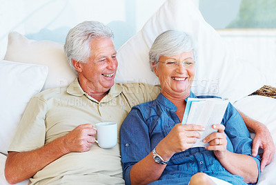 Buy stock photo Senior couple having a cup of coffee and reading book in the morning