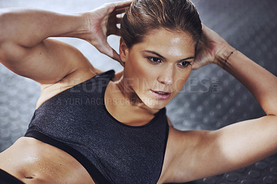 Buy stock photo Cropped shot of a young woman doing sit-ups at the gym