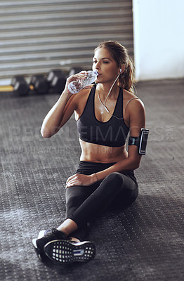 Buy stock photo Shot of a young woman working out at the gym
