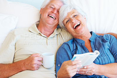Buy stock photo Portrait of senior couple having fun with man holding a cup and woman holding a book
