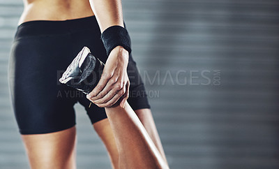 Buy stock photo Cropped rearview shot of a woman stretching her legs before a gym workout