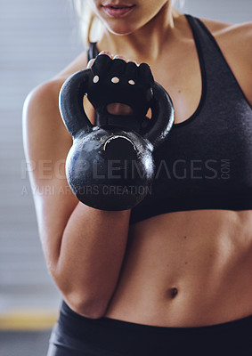 Buy stock photo Shot of a young woman working out with kettlebells