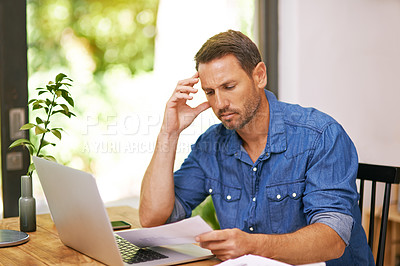 Buy stock photo Shot of a man looking over some paperwork while working from home